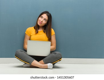 Young woman sitting on the floor with a laptop dreaming of achieving goals and purposes