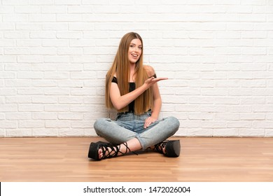 Young woman sitting on the floor extending hands to the side for inviting to come