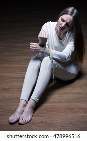 Young woman sitting on the floor with the hands tied by a centimeter