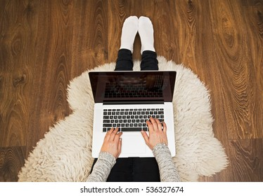 The young woman is sitting on the floor and working at laptop