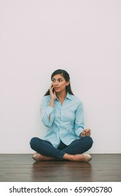 Young Woman Sitting on Floor and Calling on Phone