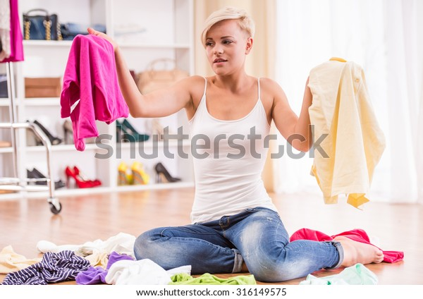 Young woman is sitting on the floor with clothes lying near her.