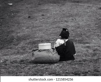 Young woman sitting on the grass in the lawn, black and white concept