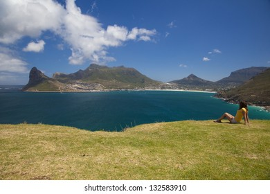 A Young Woman Sitting on the Grass, Enjoying the View Over Hout Bay, seen from a Lookout / Picnic Spot on Chapman's Peak Drive near Cape Town, South Africa.