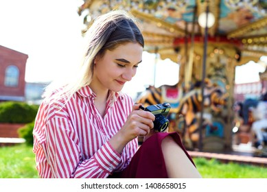 Young woman sitting on grass, with old camera and looking on it. Colorful carousel from leisure park on the background.