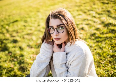 Young Woman sitting on grass in park on sunny day