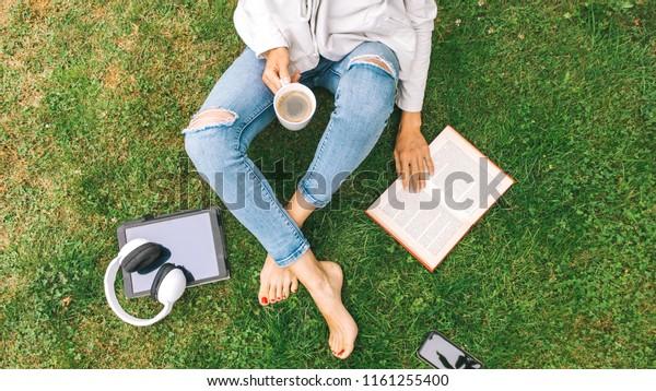 Une jeune femme assise sur l'herbe buvant du café et lisant un livre profite des loisirs de plein air.