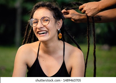 Young woman sitting on a green meadow, they're cutting her hair off with scissors. She makes many expressions with her face for the radical change of look.4