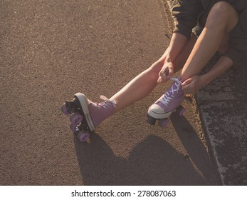 A young woman is sitting on the ground and is putting on roller skates in the park at sunset