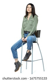 A young woman is sitting on a high chair. Female posing in jeans, boots and a khaki shirt. Isolated on white background.