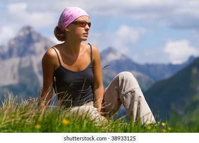 Young woman sitting on a high hill. Mountain region in Austria. Alps