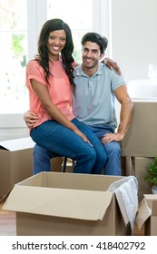Young woman sitting on lap of a man and smiling at camera in new house