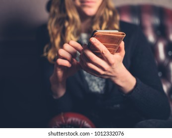 A young woman is sitting on a leather sofa and is using a smart phone