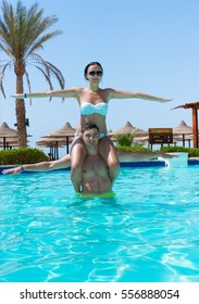 Young woman sitting on man's neck while they doing aqua fitness in swimming pool at the hotel on a sunny summer day