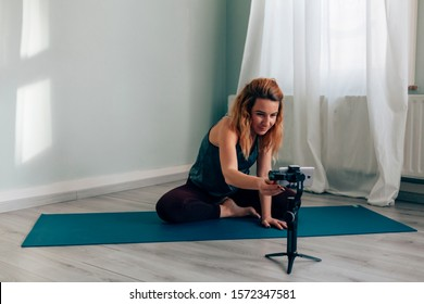 young woman sitting on mat in sportswear starting recording herself with a mobile phone on a gimbal tripod