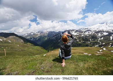 young woman sitting on  mountain slope