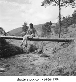 Young woman sitting on narrow footbridge over stream