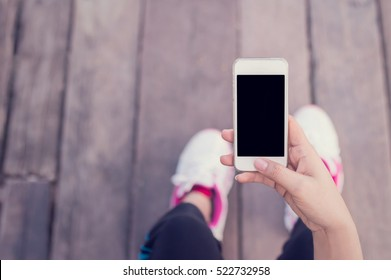 Young woman sitting on old wooden floor with hands holding smartphone with blank screen.