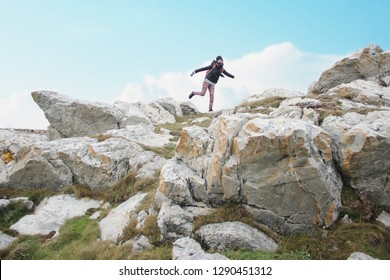 young woman sitting on one leg on the edge of the cliff