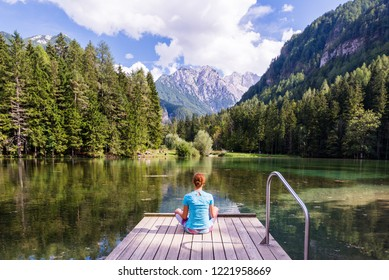 Young woman is sitting on a pier over the lake looking at the magnificent view  in Jezersko, Slovenia. Woman relaxing near the lake looking at the view. Travel adventure and freedom concept.