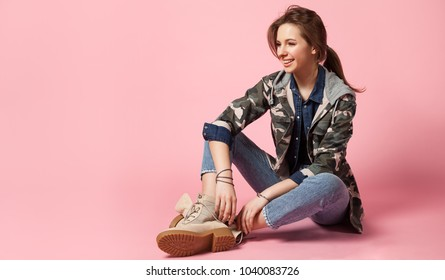 Young woman sitting on a pink background in jeans, military jacket and in rough shoes