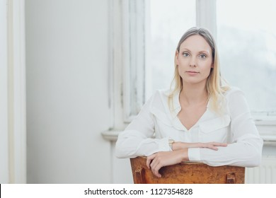 Young woman sitting on a reversed chair staring at the camera with a deadpan intense expression indoors at home with copy space