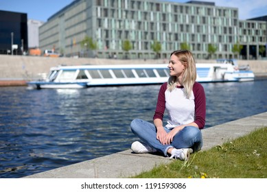 young woman sitting on river