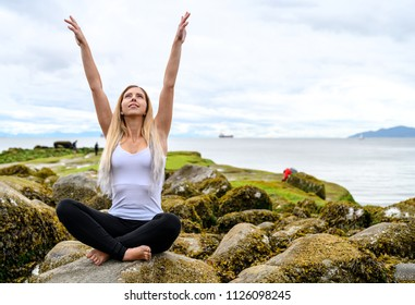 Young woman sitting on rock and her arms are raised into the air at the intertidal zone of Vancouver, British Columbia. Those rocks are underwater at high tide, and out of water at low tide.