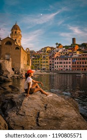 young woman sitting on a rock watching sunset at the harbour of Vernazza Cinque Terre Italy, sunset at harbor people watching village Vernazza Cinque terre