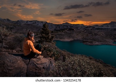 young woman sitting on rock outdoors watching a beautiful landscape of gran canaria island during sunset