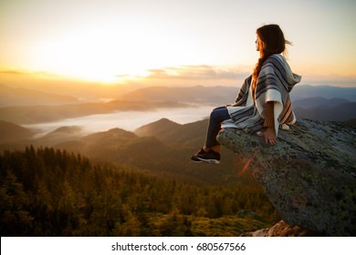 Young woman sitting on a rock and looking to the horizon. Hipster young girl with backpack enjoying sunset on peak mountain. Wonderful landscape with cloud inversion.
