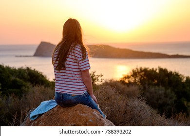 Young woman sitting on a rock, enjoying a peaceful moment of sunset with sea and mountain views