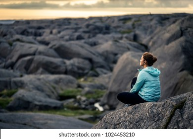 Young woman is sitting on the rocks during the sunset and meditating. Norway.