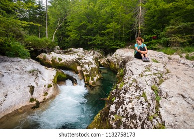 Young woman is sitting on the rocks looking at the turquoise river in Koritnica gorge near Bohinj, Slovenia