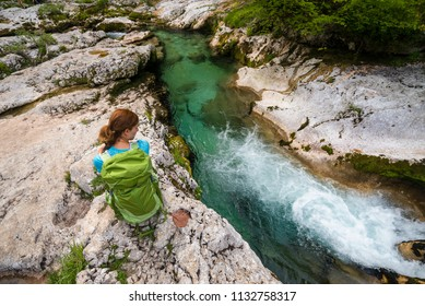 Young woman is sitting on the rocks wearing green backpack and looking at the turquoise river in Koritnica gorge near Bohinj, Slovenia