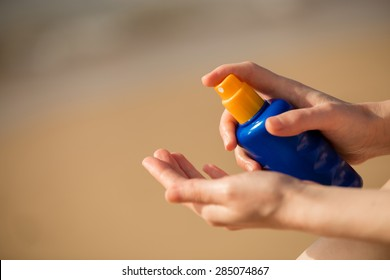 Young woman sitting on sand seashore, holding bottle of sunscreen lotion before applying, close up of hands