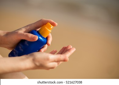 Young woman sitting on sand seashore, holding bottle of sunscreen lotion before applying on tropical beach holiday, close up of hands. Skincare concept