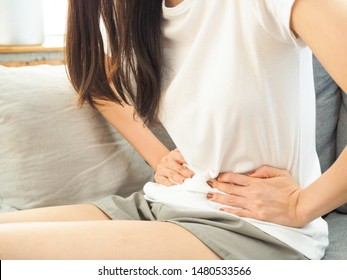 Young woman sitting on sofa and feeling stomachache or menstrual syndrome or woman stomachache, menstrual syndome, women's health concept. with copy space