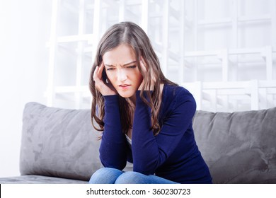 Young Woman Sitting On Sofa having headache migraine. Stress and depression.