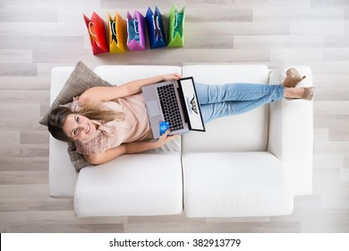 Young Woman Sitting On Sofa With Laptop Shopping Online