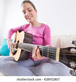 Young woman sitting on the sofa, smiling and playing acoustic guitar in her living room.