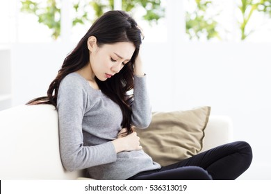 Young woman sitting on sofa and having stomachache