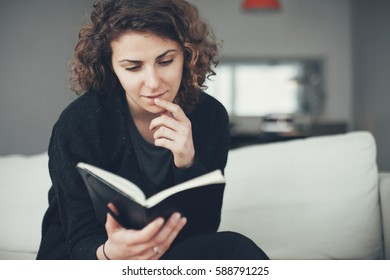 Young woman sitting on the sofa with open book and reading with interest. Soft focus image