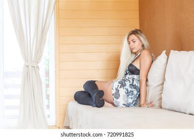 Young woman sitting on a sofa, relaxing. Blonde female model in black stockings is waiting for something in autumn evening.