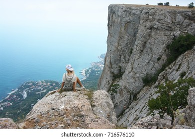 Young woman sitting on steep cliff and looking at landscape. Back view.