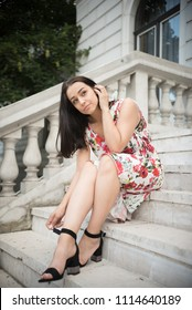 young woman sitting on steps and looking in distance