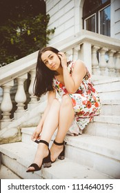 young woman sitting on steps and holding little belt on her shoe