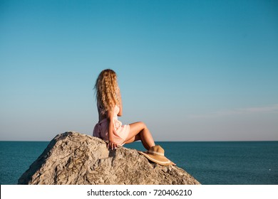 Young woman sitting on stone, sea view. Fashion clothes, straw hat, blonde long hair.  Freedom and happiness concept. Holidays time.