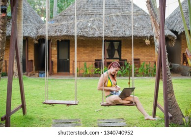 A young woman is sitting on a swing with a laptop. Work and travel. Cozy bungalows