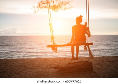 Young woman sitting on a swing at the beach.